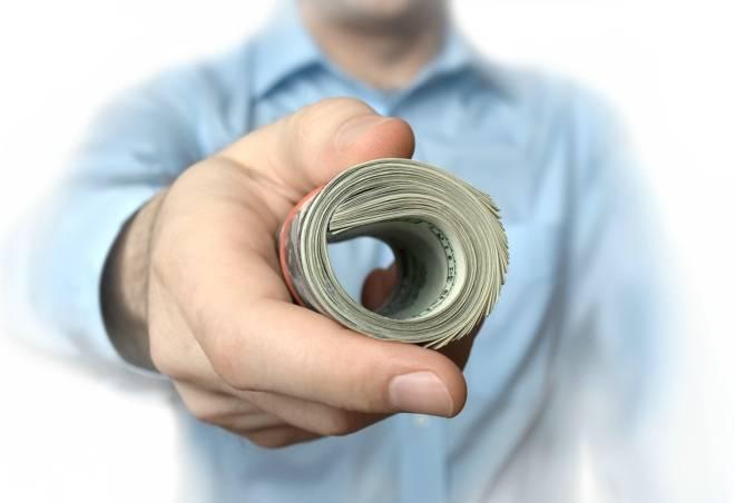 Man-Handing-Over-Roll-of-Dollars