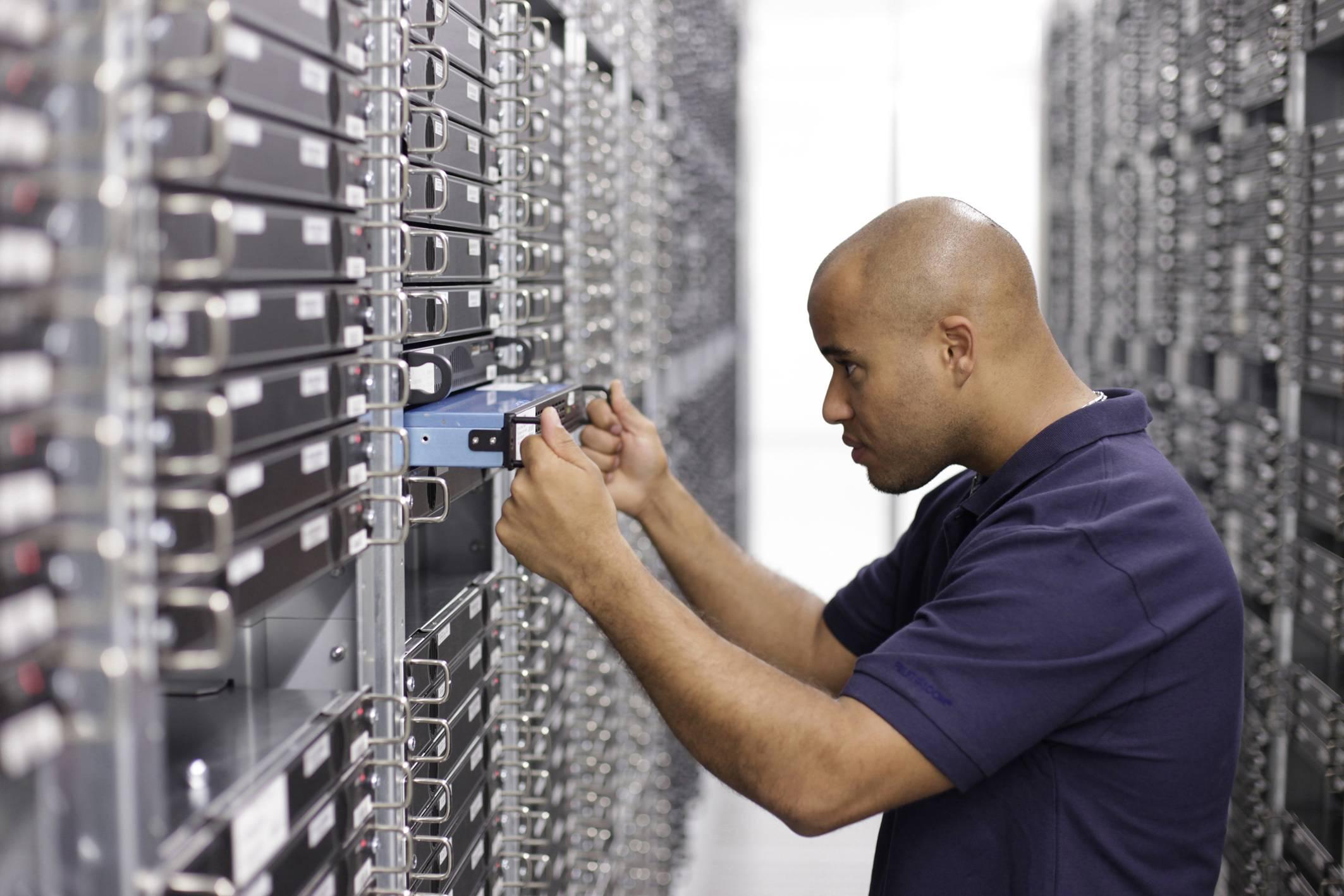 STRATO Mitarbeiter hebt einen Server zurück in ein Rack