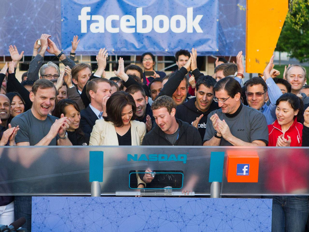 In this image provided by Facebook, Facebook founder, Chairman and CEO Mark Zuckerberg, center, rings the opening bell of the Nasdaq stock market, Friday, May 18, 2012, from Facebook headquarters in Menlo Park, Calif. The social media company priced its IPO on Thursday at $38 per share, and beginning Friday regular investors will have a chance to buy shares. (AP Photo/Nasdaq via Facebook, Zef Nikolla)