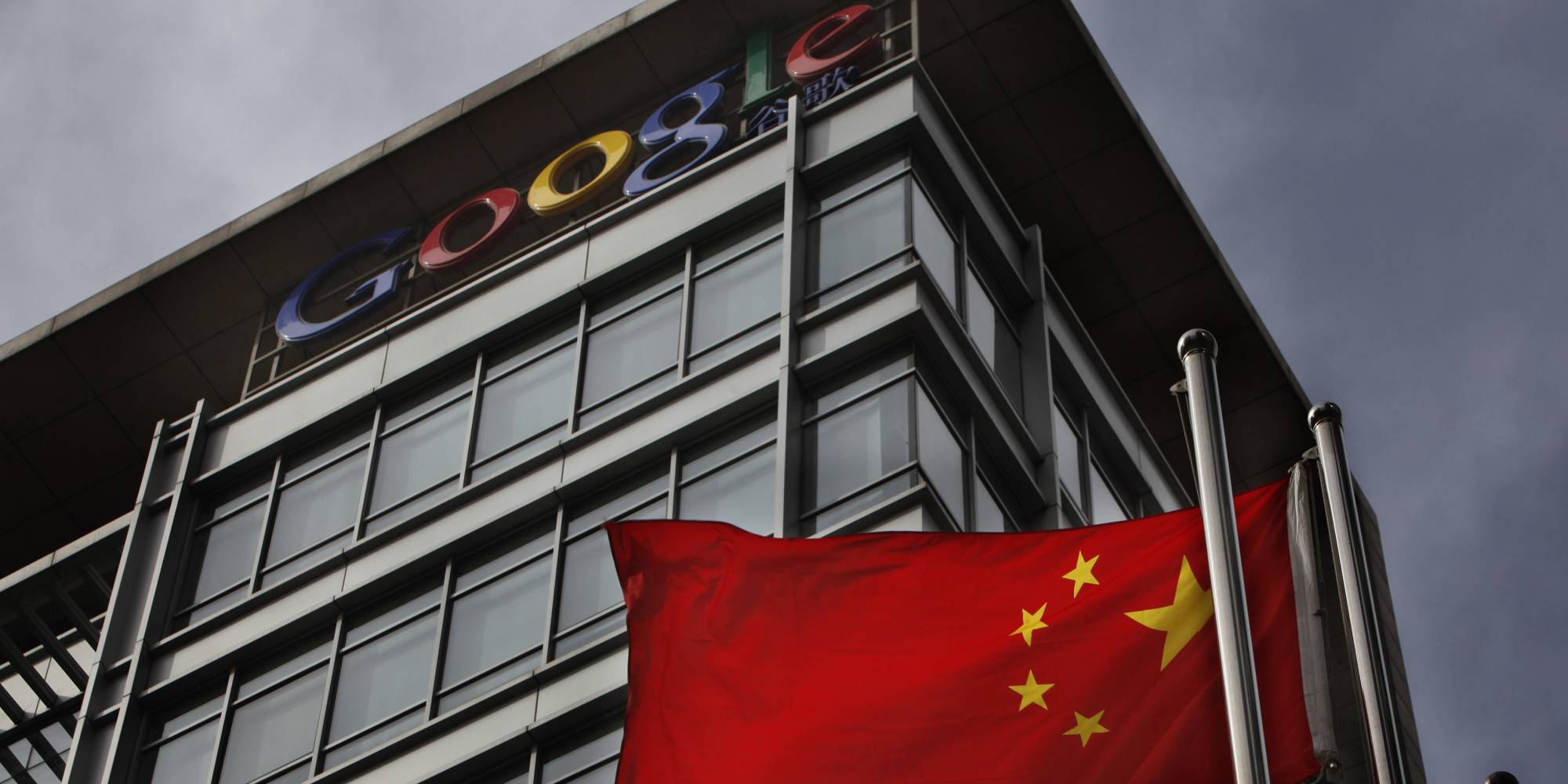 A Chinese flag blows in the air below the Google logo outside the Google China headquarters in Beijing Thursday, March 25, 2010. While Google's decision to move its Chinese search engine offshore challenging China's online censorship laws win praise in the U.S. and other countries, it's threatening to turn the company into a pariah in China. (AP Photo/ Gemunu Amarasinghe)