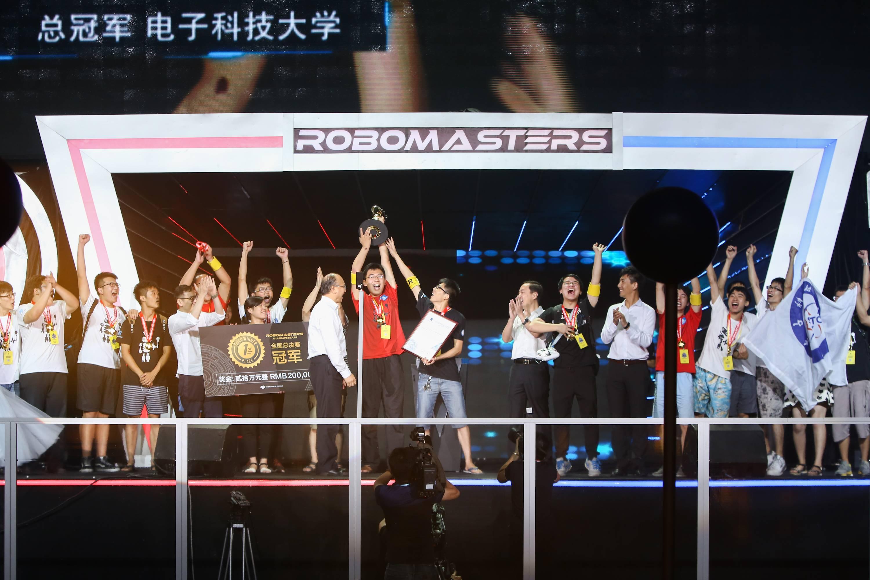 汪滔(手捧冠军奖金牌的女孩右手边的男子)参加了冠军颁奖仪式,他热衷于这样的场合
