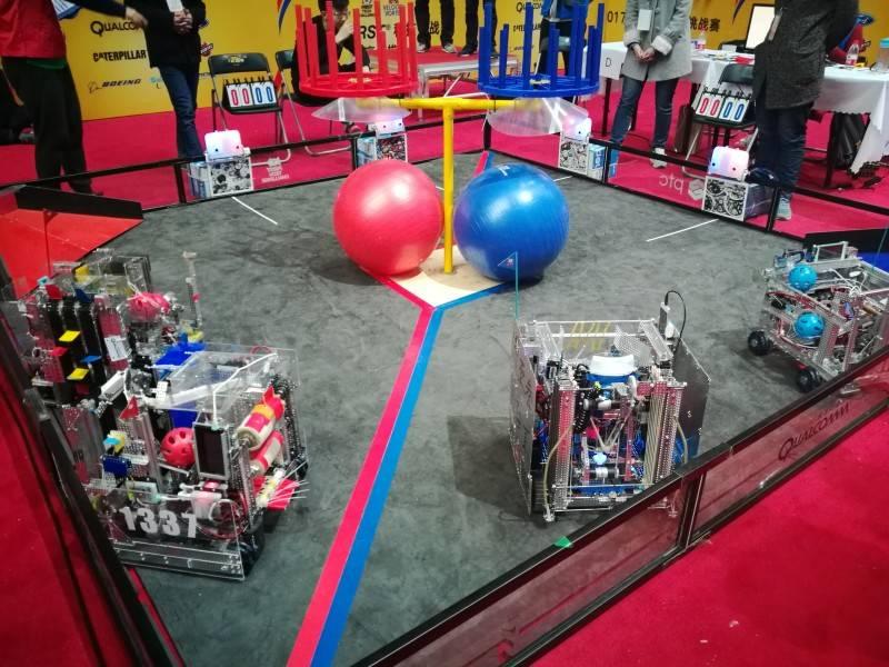 (赛场由中心区的自由旋转旋涡和角区旋涡组成,以联盟作战(2:2)操控机器人投球、抓举大球完成指定和自选动作以得分。)