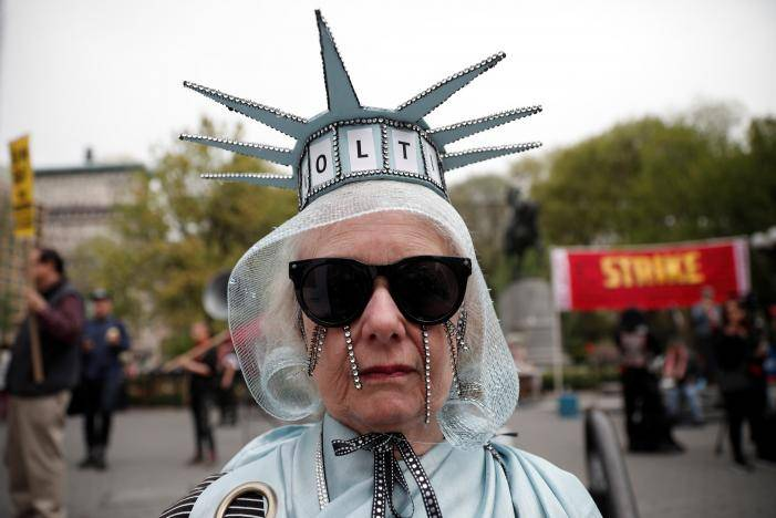 A woman stands dressed as the Statue of Liberty during a May Day protest in New York