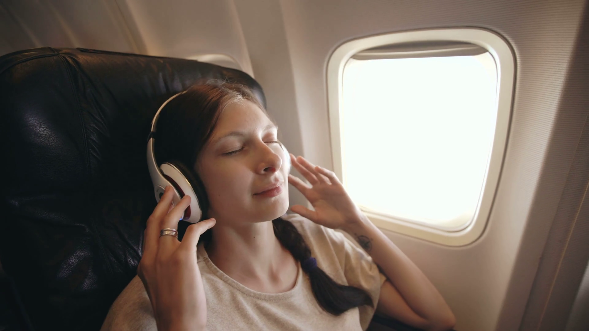 videoblocks-young-woman-in-wireless-headphones-listening-to-music-and-smiling-during-fly-in-airplane_sgqpxsfhe_thumbnail-full01