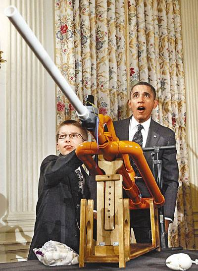 U.S. President Barack Obama reacts as Joey Hudy of Phoenix, Arizona, launches a marshmallow from his Extreme Marshmallow Cannon in the State Dining Room of the White House during  the second White House Science Fair in Washington February 7, 2012. The fair celebrates the achievements of student winners of a broad range of science, technology, engineering and math (STEM) competitions from across the country.  REUTERS/Kevin Lamarque  (UNITED STATES - Tags: SCIENCE TECHNOLOGY SOCIETY TPX IMAGES OF THE DAY EDUCATION)