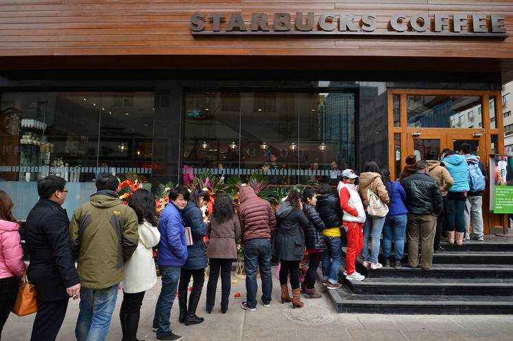 TAIYUAN, CHINA - MARCH 01: (CHINA OUT) People line up to buy coffee during a Starbucks Coffee shop opening ceremony on March 1, 2013 in Taiyuan, China. Taiyuan's first Starbucks officially opened today. The coffee shop is located on the first floor of Maoye Department Store. (Photo by ChinaFotoPress/ChinaFotoPress via Getty Images)