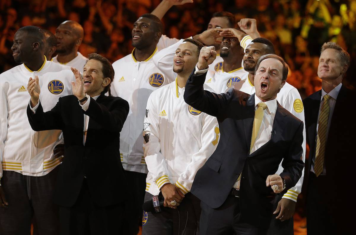 Golden State Warriors co-owner Joe Lacob, front right, reacts beside Stephen Curry and co-owner Peter Guber, second from left, as the Warriors championship banner is revealed during an awards ceremony to recognize the Warriors' NBA championship prior to a basketball game against the New Orleans Pelicans, Tuesday, Oct. 27, 2015, in Oakland, Calif. At right is Warriors coach Steve Kerr. (AP Photo/Ben Margot)