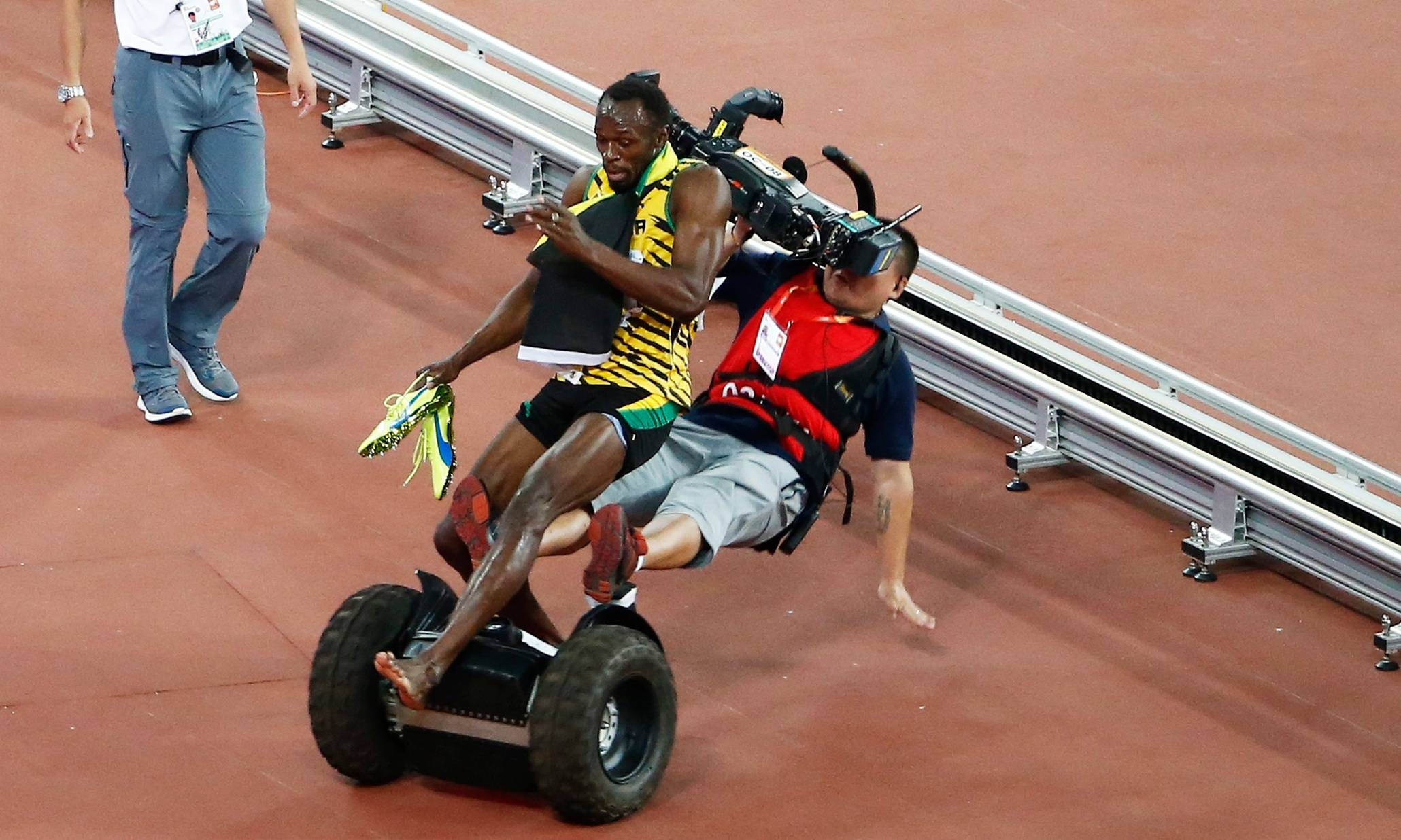 epa04900474 A Tv cameraman drives into Usain Bolt of Jamaica after the men's 200m final during the Beijing 2015 IAAF World Championships at the National Stadium, also known as Bird's Nest, in Beijing, China, 27 August 2015. Bolt won the race. EPA/ROLEX DELA PENA