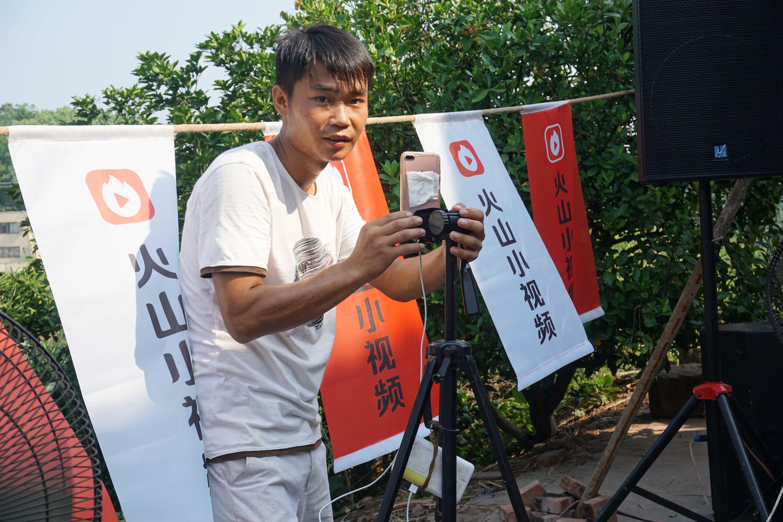 在烈日下直播的刘金银,为了给手机降温,用餐巾纸蘸水贴在手机背面。摄影吴绛枫。
