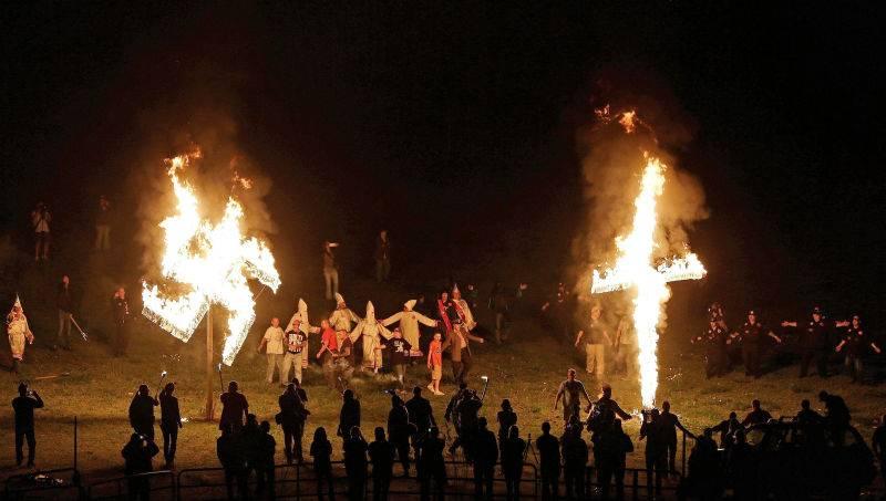 """带有三K党色彩的社团""""忠诚白骑士"""",其成员周六晚间在夏洛茨维尔焚烧十字架和万字标志 / 美联社"""